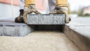 Paving slabs being laid on top of a prepared paving sand base
